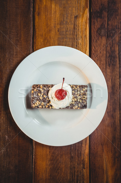 Stock photo: Pastry with whipped cream and cherry topping on plate