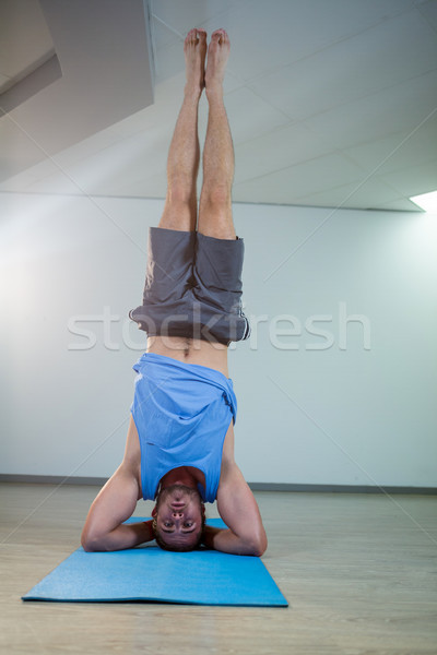 Man performing sirsasana on exercise mat Stock photo © wavebreak_media