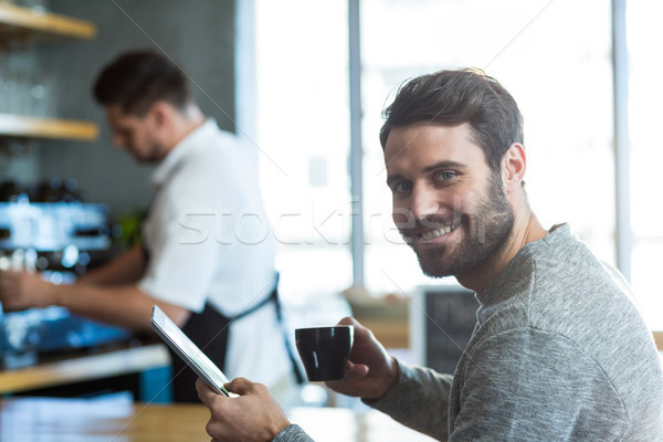 Smiling man using mobile phone while having cup of coffee in café Stock photo © wavebreak_media