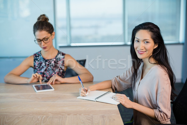 Sorridere business colleghi iscritto notepad digitale Foto d'archivio © wavebreak_media