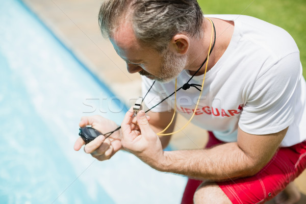 Swim coach looking at stop watch near poolside Stock photo © wavebreak_media