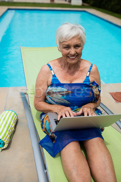 Portrait of senior woman using laptop on lounge chair Stock photo © wavebreak_media