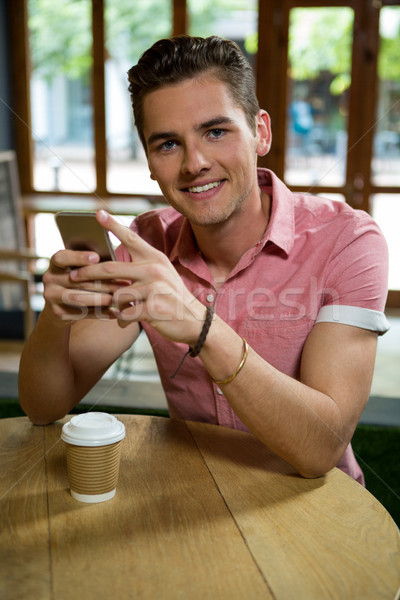 Stock photo: Handsome young man using mobile phone in cafe