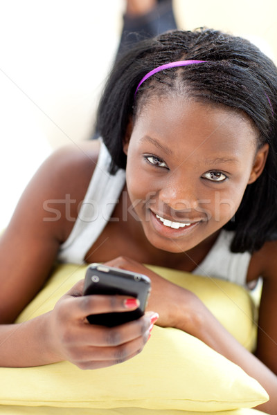 Attractive woman sending a text lying on a sofa Stock photo © wavebreak_media