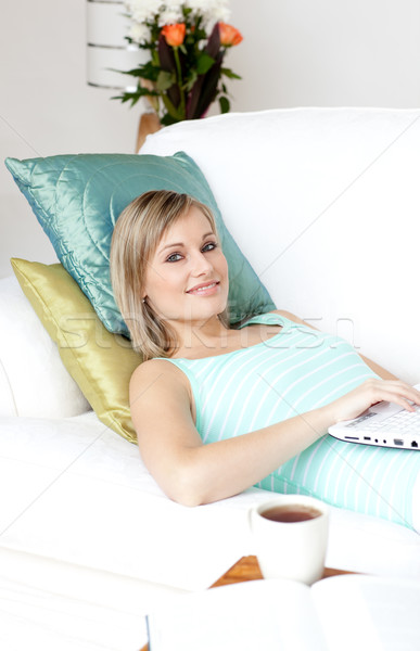Radiant woman using a laptop lying on a sofa Stock photo © wavebreak_media
