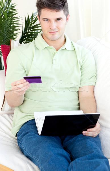 харизматический молодым человеком карт ноутбука диван улыбаясь Сток-фото © wavebreak_media