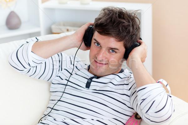 Foto d'archivio: Divertente · uomo · ascolto · musica · cuffie · seduta