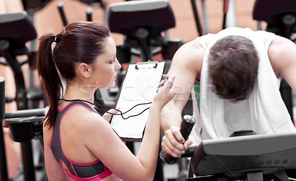 Female coach using a chronometer while man is pedaling on a bicycle in a fitness centre Stock photo © wavebreak_media