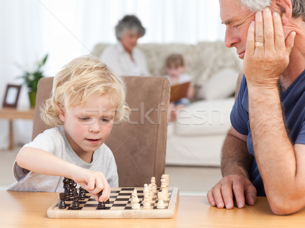 Young boy playing chess with his grandfather at home Stock photo © wavebreak_media