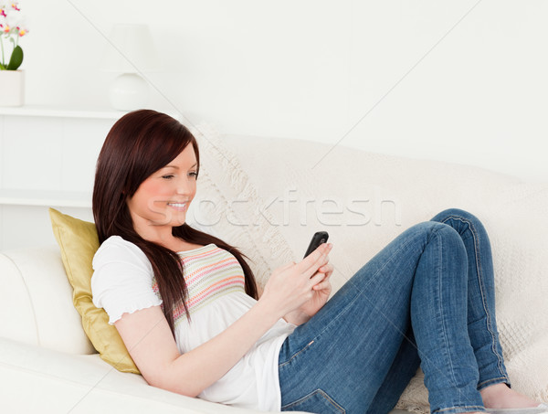 Beautiful red-haired woman writing a text on her phone while lying on a sofa in the living room Stock photo © wavebreak_media