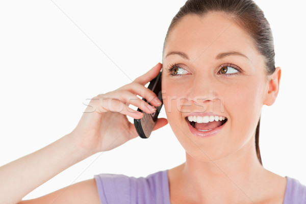 Portrait of a good looking woman on the phone while standing against a white background Stock photo © wavebreak_media