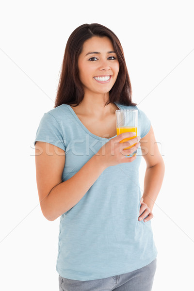 Beautiful woman holding a glass of orange juice while standing against a white background Stock photo © wavebreak_media