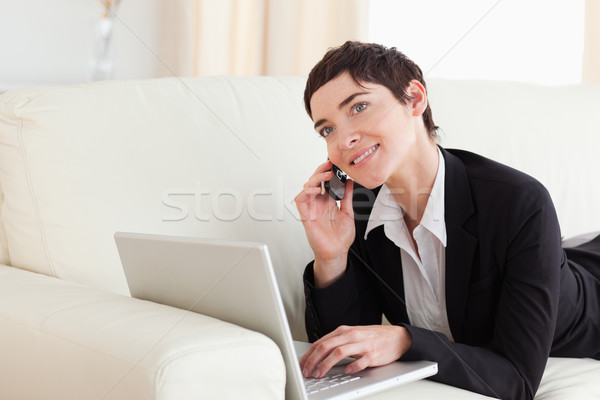 Charming Woman lying on a sofa with a laptop and a phone in the living room Stock photo © wavebreak_media