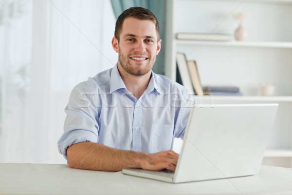 Smiling businessman with rolled up sleeves on his laptop in his homeoffice Stock photo © wavebreak_media