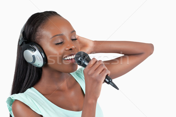 Young woman enjoys singing against a white background Stock photo © wavebreak_media