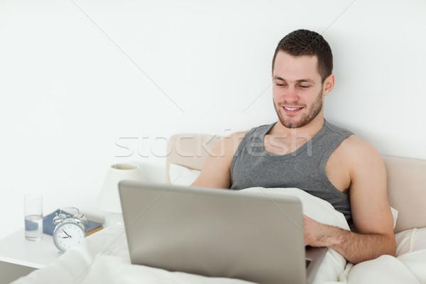 Pacífico hombre usando la computadora portátil dormitorio ordenador feliz Foto stock © wavebreak_media
