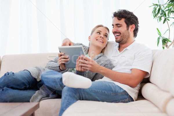 Delighted couple using a tablet computer in their living room Stock photo © wavebreak_media