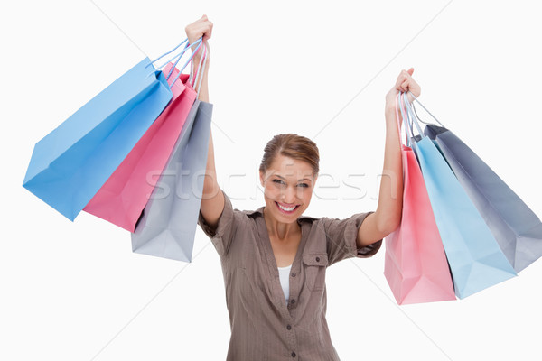 Happy woman raising her shopping bags against a white background Stock photo © wavebreak_media