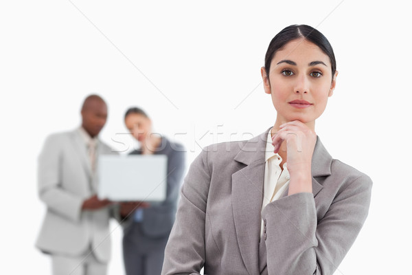 Thinking saleswoman with colleagues behind her against a white background Stock photo © wavebreak_media