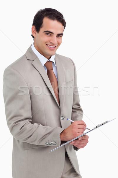 Sorridente vendedor bloco de notas caneta branco trabalhar Foto stock © wavebreak_media