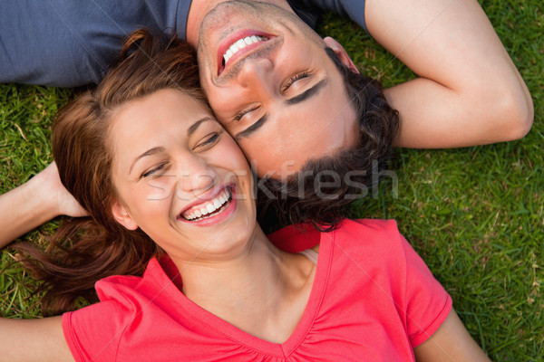 Two friends smiling with their eyes closed while lying head to shoulder with an arm behind their hea Stock photo © wavebreak_media