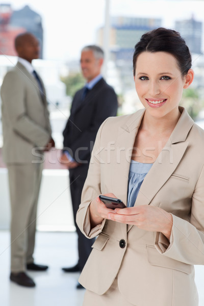 Smiling secretary standing in front of executives while sending a text Stock photo © wavebreak_media