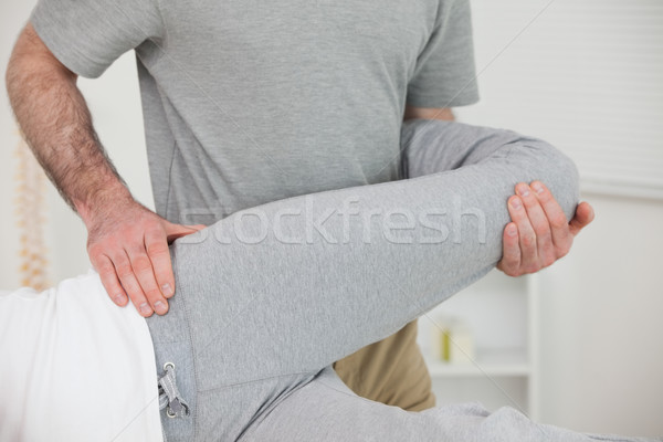 Chiropractor stretching the leg of a patient in a room Stock photo © wavebreak_media