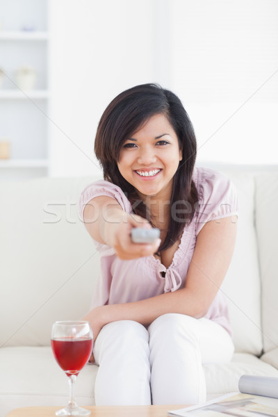 Woman smiling and holding a television remote in a living room Stock photo © wavebreak_media