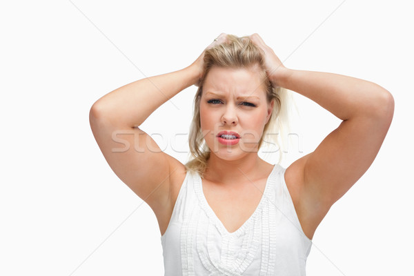 Upset woman standing while placing her hands on her head against a white background Stock photo © wavebreak_media