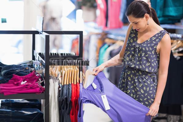 Donna guardando prezzo tag viola shirt Foto d'archivio © wavebreak_media