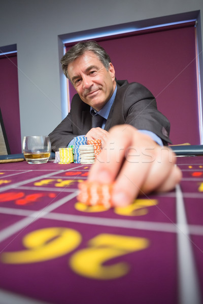 Hombre sesión sonriendo casino vidrio Foto stock © wavebreak_media
