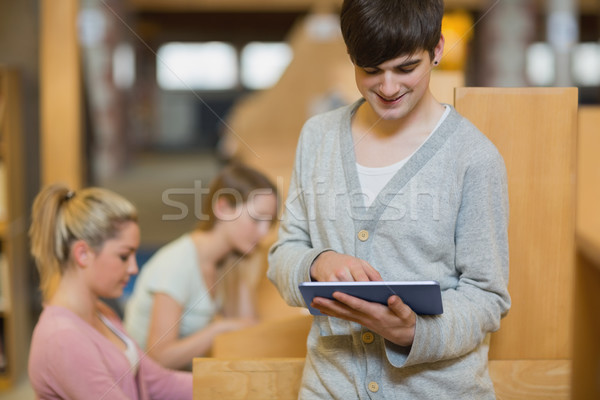 Man standing in college library holding a tablet computer while smiling  Stock photo © wavebreak_media
