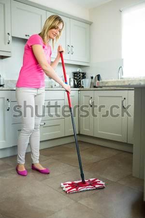 Woman standing holding a vacuum cleaner wearing headphones Stock photo © wavebreak_media