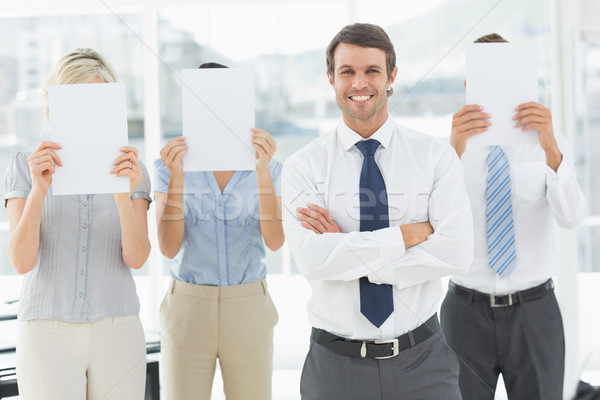 Businessman with colleagues holding blank paper in front of face Stock photo © wavebreak_media