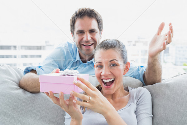 Man surprising his delighted girlfriend with a pink gift on the  Stock photo © wavebreak_media