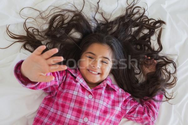 High angle portrait of smiling girl lying in bed Stock photo © wavebreak_media