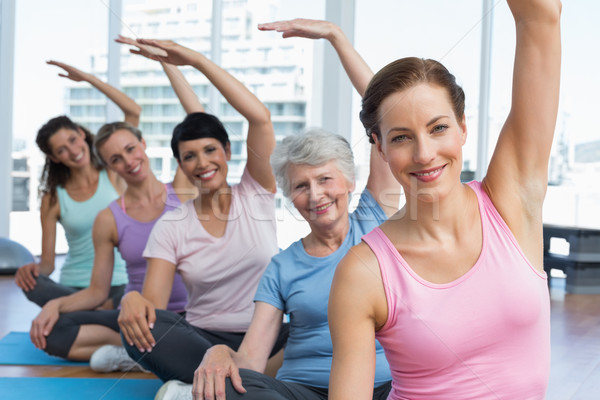 Stock photo: Trainer with women in row stretching hands at yoga class