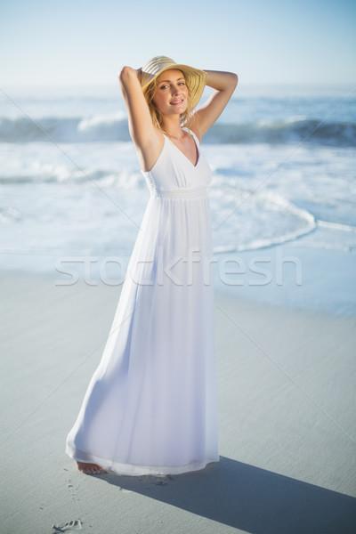 Smiling blonde standing at the beach in white sundress and sunha Stock photo © wavebreak_media