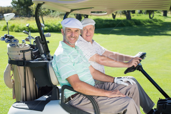Golfing friends smiling at camera in their golf buggy Stock photo © wavebreak_media