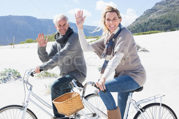 Carefree couple going on a bike ride on the beach waving at came Stock photo © wavebreak_media