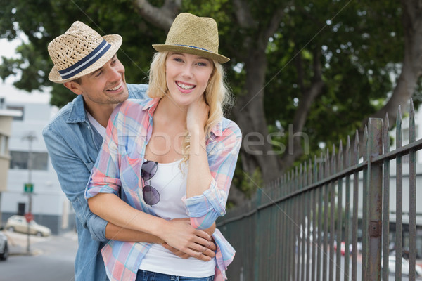 Hip young couple smiling at camera by railings Stock photo © wavebreak_media