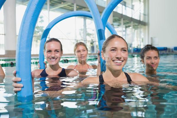 Female fitness class doing aqua aerobics with foam rollers Stock photo © wavebreak_media