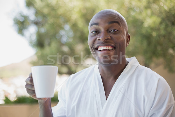 Handsome man in bathrobe having coffee outside Stock photo © wavebreak_media