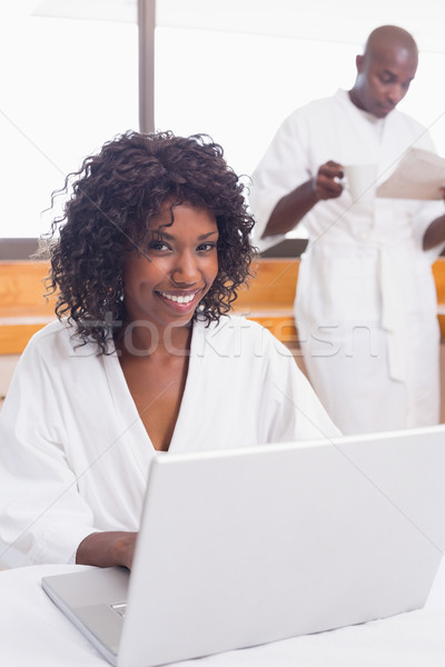 Pretty woman in bathrobe using laptop at table with partner in b Stock photo © wavebreak_media