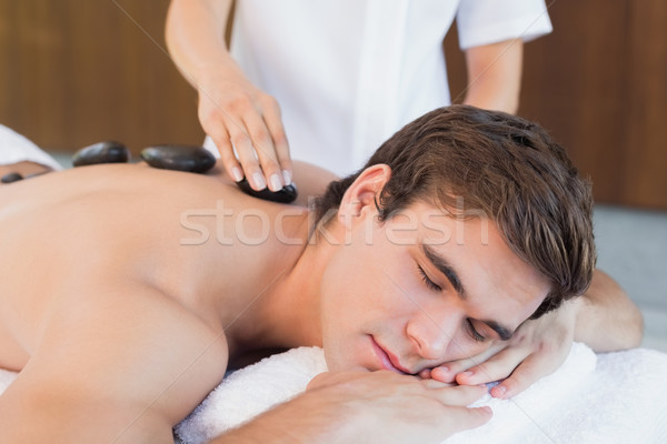 Stock photo: Young man receiving stone massage at spa center