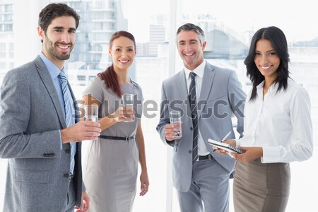 Businesswoman text messaging with colleagues in meeting behind Stock photo © wavebreak_media