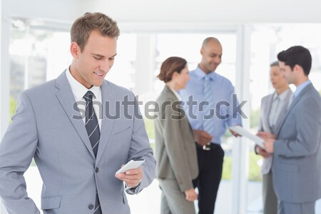 Businessman text messaging with colleagues in meeting behind Stock photo © wavebreak_media