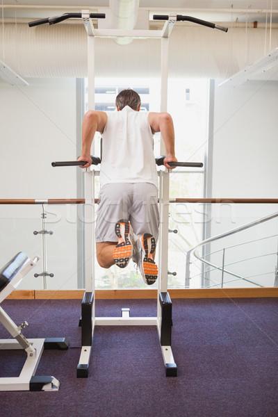 Fit man doing pull ups in fitness studio Stock photo © wavebreak_media