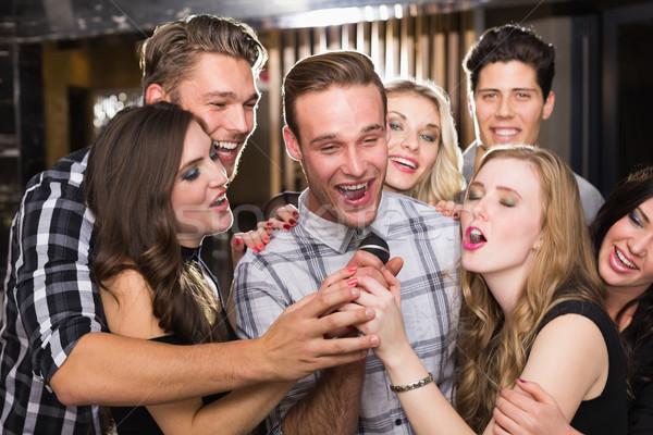 Happy friends singing karaoke together Stock photo © wavebreak_media