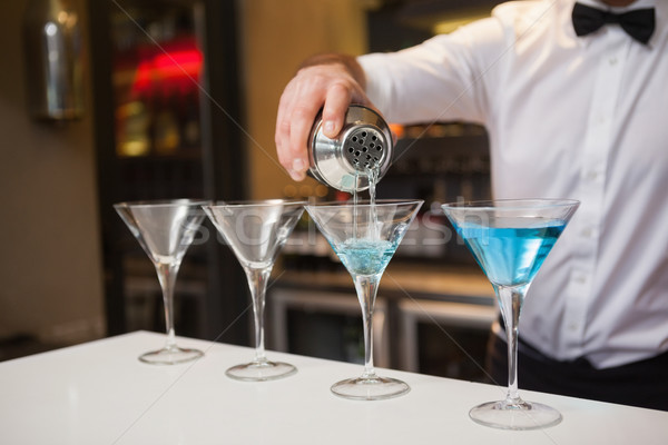 Bartender pouring blue alcohol into cocktail glass Stock photo © wavebreak_media